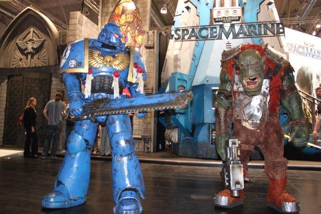 Ein Space Marine und ein Ork duellieren sich vor dem THQ-Stand.