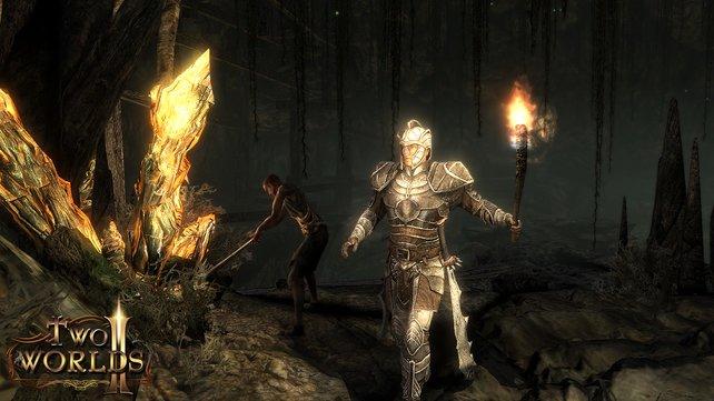 Mit der Fackel in der Hand pirscht der Held durch eine Höhle.