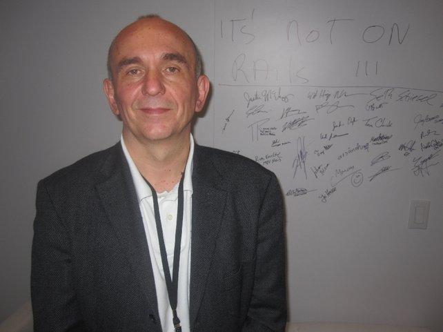 """Peter Molyneux vor seiner """"Das neue Fable ist spielbar""""-Wand. In der Mitte unten hat auch Jo Hesse unterschrieben."""