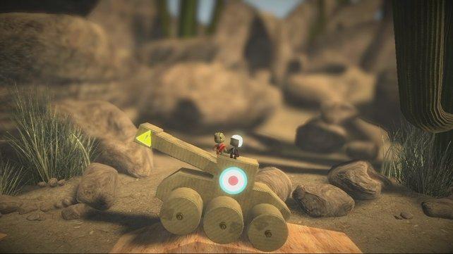 Zwei Sackpuppen fahren mit einem Holzpanzer durch das Level.
